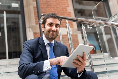 empresarios: Apuesto hombre de negocios sentado en los escalones con tablet pc Foto de archivo