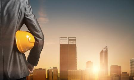 traje formal: Cierre para arriba del hombre en traje con casco de construcción y guantes en la mano