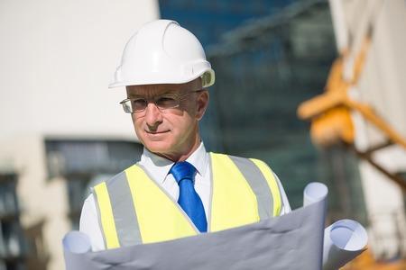 ingeniero: Ingeniero de construcci�n en sombrero duro con el proyecto en las manos