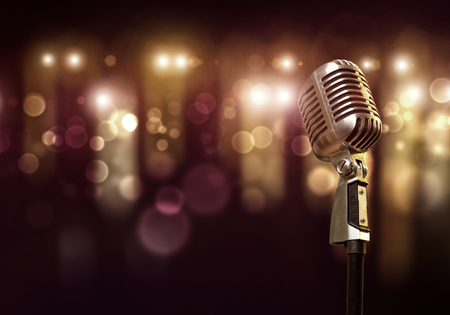 entertainment: Close up of microphone in concert hall with blurred lights at background Stock Photo