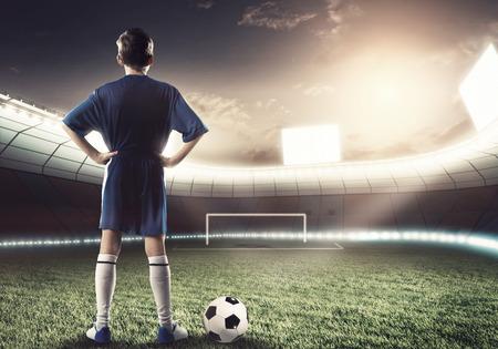 Achteraanzicht van football-speler op het stadion klaar om aan te vallen poorten