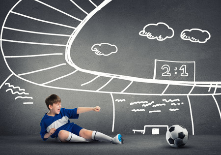 school aged: School aged boy on sketched background playing football Stock Photo