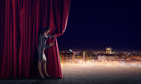stage: Young woman in business suit opening color curtain of stage