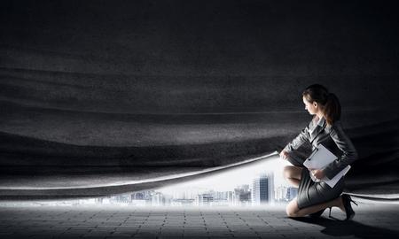 セメント カーテンを開くビジネス スーツの若い女性