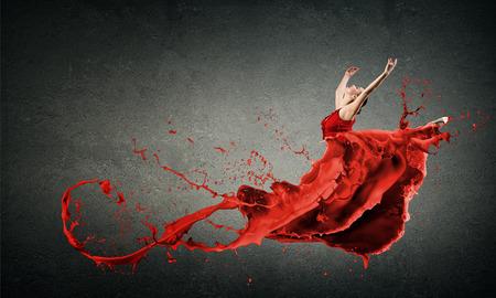 빨간 드레스와 빨간 spalshes에서 열정적 인 여자 댄서