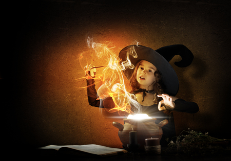 conjure: Little Halloween witch reading conjure from magic book above pot Stock Photo