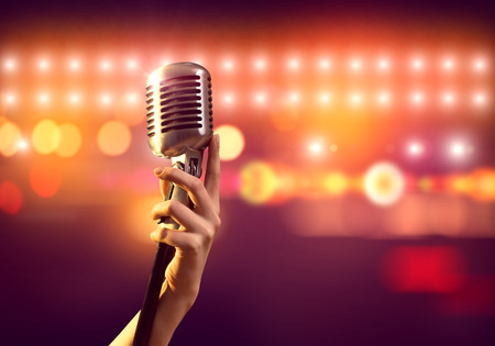concert stage: Close up of female hand on blurred background holding microphone Stock Photo