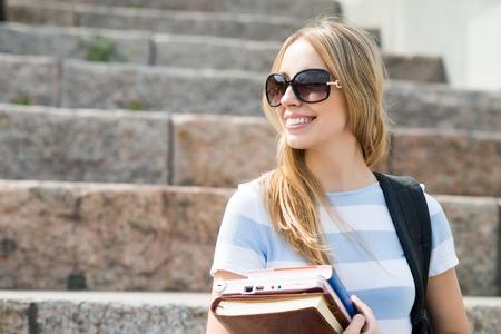 階段の上に座って、書籍で勉強し、大学生の笑顔