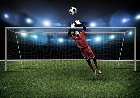 goalkeeper: Goalkeeper in gates jumping to catching ball Stock Photo