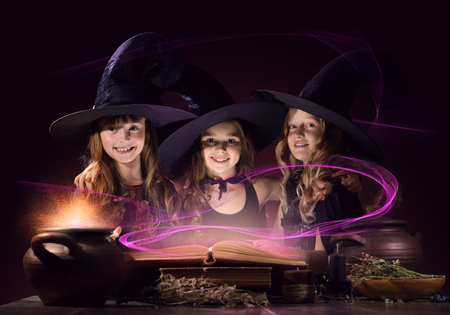 conjure: Three little Halloween witches reading conjure from magic book