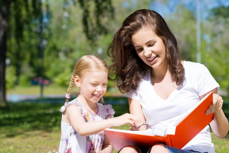 teacher: girl with the teacher reading a book together in the summer park