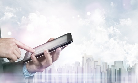 computer device: Close up of businessman using tablet pc and city landscape at background
