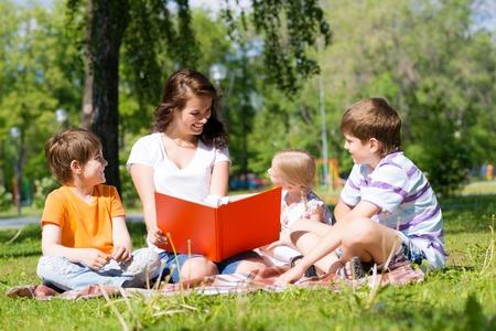 preescolar: ni�os y profesor de leer el libro juntos en el parque de verano