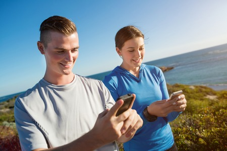 такса: Young couple on beach checking heart rate after run