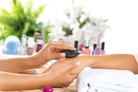 manicure salon: Woman in salon receiving manicure by nail beautician
