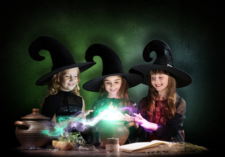 conjure: Three little Halloween witches reading conjure from magic book above pot
