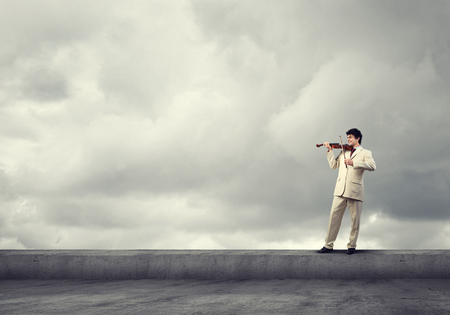 roof: Young businessman on roof top playing violin Stock Photo