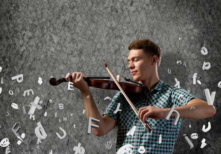 violin player: Young handsome guy on cement background with violin