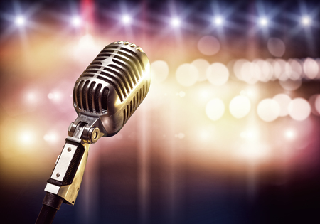 Close up of microphone in concert hall with blurred lights at background Foto de archivo