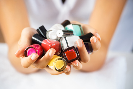 red nail colour: Close up of woman hands with nail polishes of different colors Stock Photo