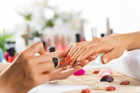 nail studio: Woman in salon receiving manicure by nail beautician