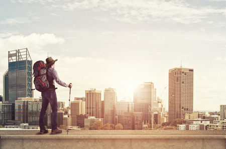 outdoorsman: Young man hiker standing on top of city building Stock Photo