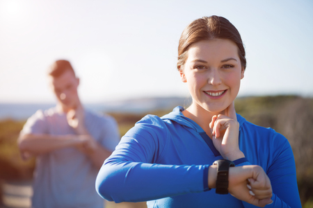 outdoor training: Young couple on beach checking heart rate after run