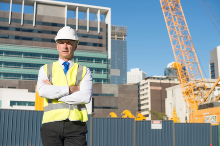 engineer: Confident construction engineer in hardhat with arms crossed on chest