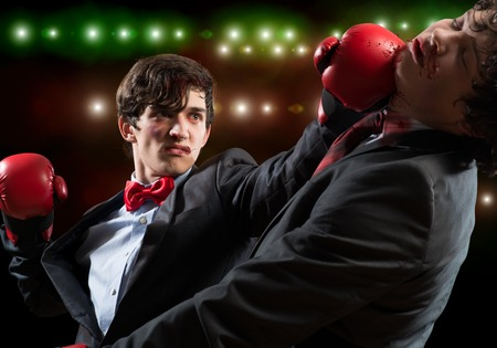 agression: Two businessman in boxing gloves in ring fighting with each other