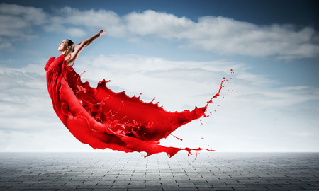 Passionate woman dancer in red dress and red spalshes