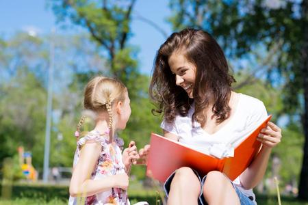 maestro: chica con el profesor de lectura un libro juntos en el parque de verano
