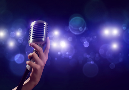 karaoke: Close up of female hand on blurred background holding microphone Stock Photo