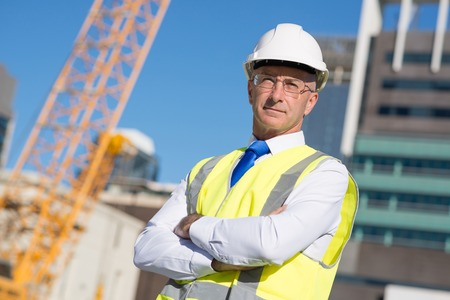 engineering design: Confident construction engineer in hardhat with arms crossed on chest