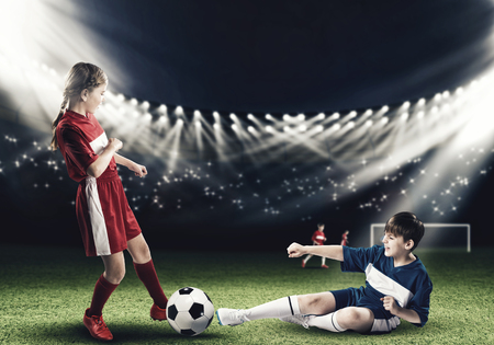female feet: Two teens of school age playing football on stadium