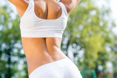 loss weight: Close up of young sport woman standing in sunny park Stock Photo