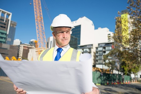 contractor: Construction engineer in hardhat with project in hands