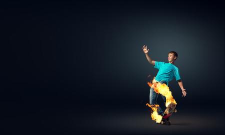skater boy: Skater boy riding on his skateboard burning in fire Stock Photo