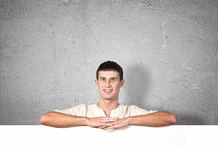 ad: Portrait of handsome male holding blank white ad board