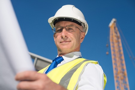 construction worker: Construction engineer in hardhat with project in hands