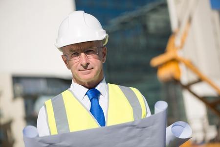 ingeniero: Ingeniero de construcción en sombrero duro con el proyecto en las manos