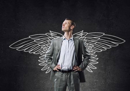 ange gardien: Jeune homme d'affaires � la craie dessin� ailes derri�re le dos Banque d'images