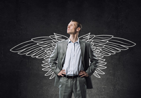 guardian: Young businessman with chalk drawn wings behind his back