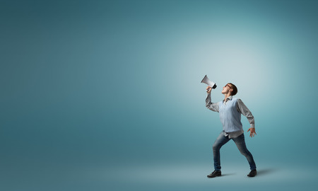 Teenager boy in glasses screaming emotional in megaphone Stock Photo - 48096685
