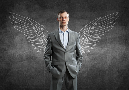 Young businessman with chalk drawn wings behind his back