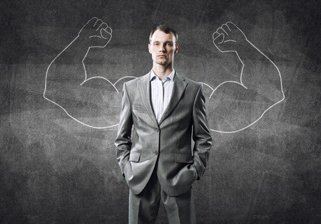 dominance: Businessman with strong arms drawn with chalk behind his back