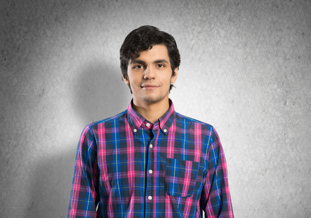 checked shirt: Young handsome man in checked shirt on concrete background Stock Photo