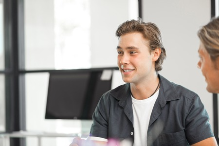 teamworking: Young colleagues sitting at desk and having discussion in bright office