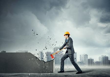 business tool: Young businessman in helmet breaking cement wall with axe
