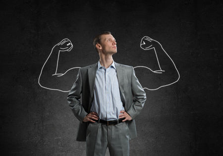 Businessman with strong arms drawn with chalk behind his back