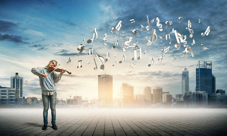 playful behaviour: Teenager boy playing violin on cityscape background
